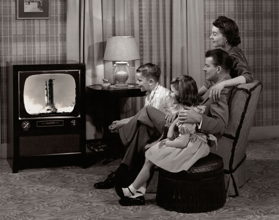 Family sits in front of television to witness an Apollo mission.